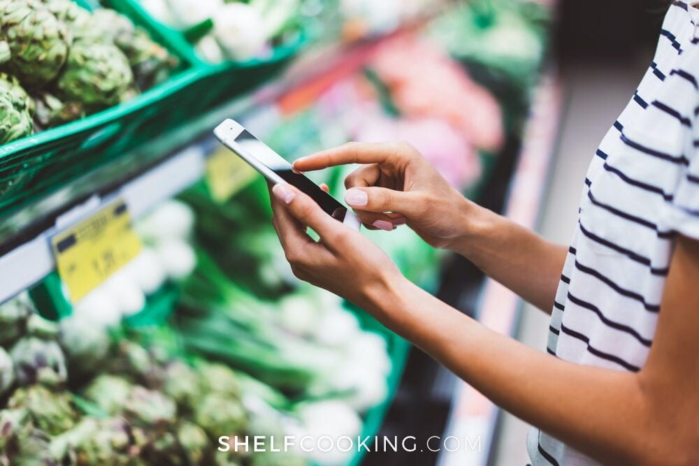 Woman adding grocery prices to her phone, from Shelf Cooking
