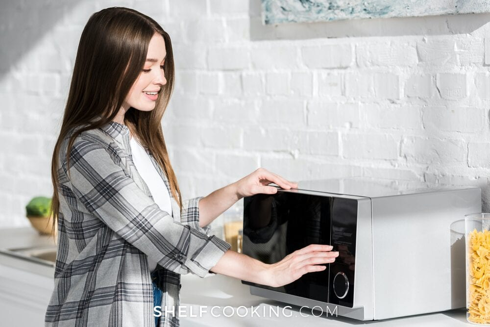 Woman using microwave to reheat leftovers, from Shelf Cooking