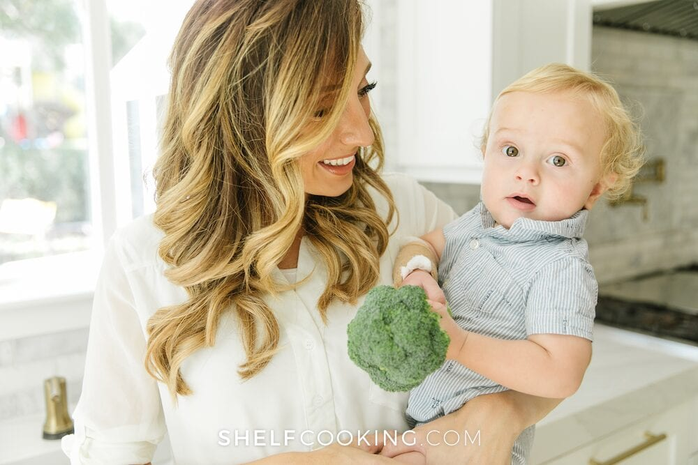 Jordan Page holding baby and broccoli, from Shelf Cooking