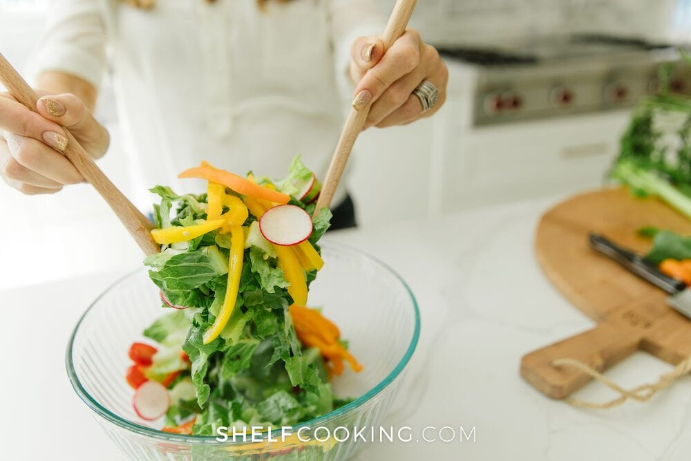 Hands tossing a salad in a glass bowl, from Shelf Cooking