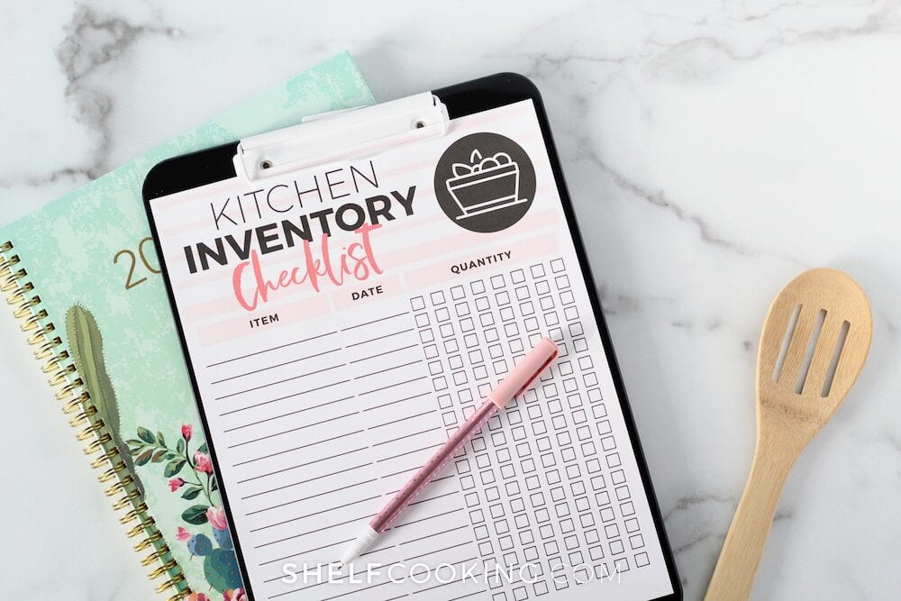 Kitchen inventory checklist, planner and wooden spoon on a counter, from Shelf Cooking