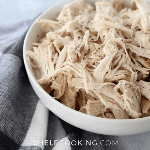 Instant Pot shredded chicken in a white bowl, from Shelf Cooking