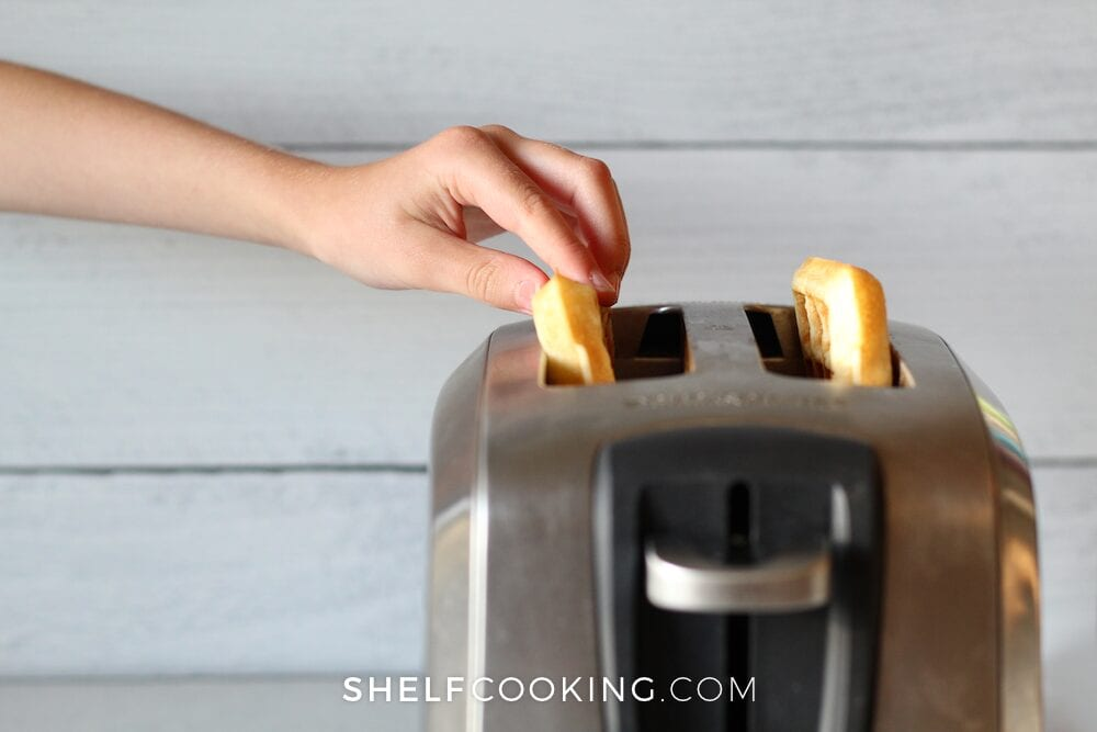 Hand putting a make ahead breakfast waffle in the toaster, from Shelf Cooking