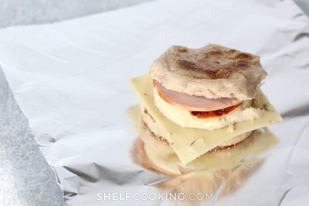 Breakfast egg sandwich sitting on foil, from Shelf Cooking