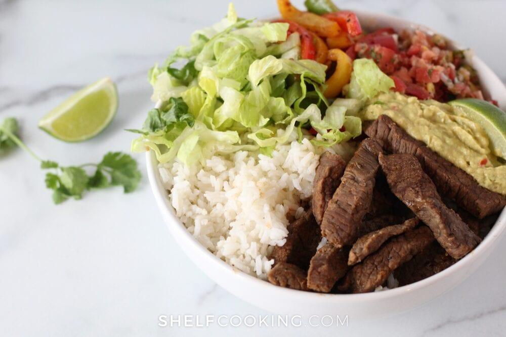 Steak, lettuce, rice, guacamole, and pico de gallo in a bowl, from Shelf Cooking