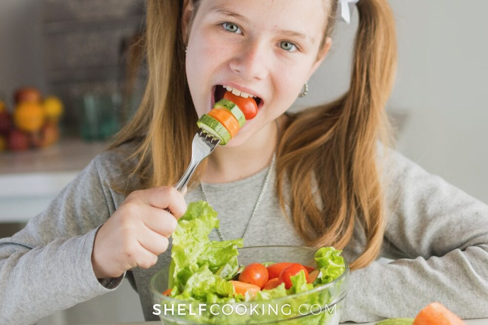 Tween girl eating salad from a bowl, from Shelf Cooking