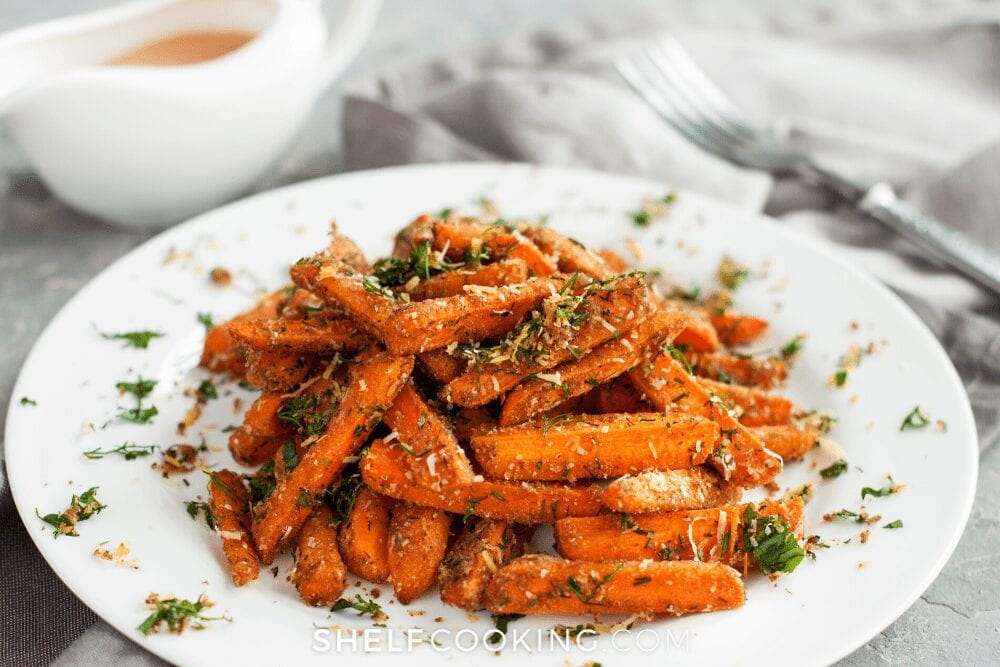 Roasted carrots on a plate with herbs from Shelf Cooking