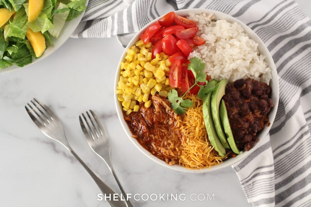 Copycat Cafe Rio sweet pork rice bowl on a counter, from Shelf Cooking