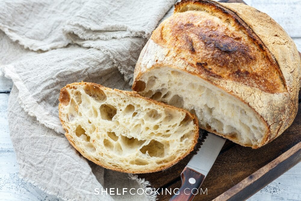 Rustic bread recipe on a cutting board with a bread knife, from Shelf Cooking