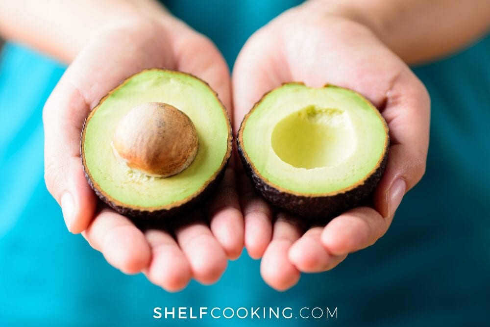 Hands holding an avocado cut in half, from Shelf Cooking