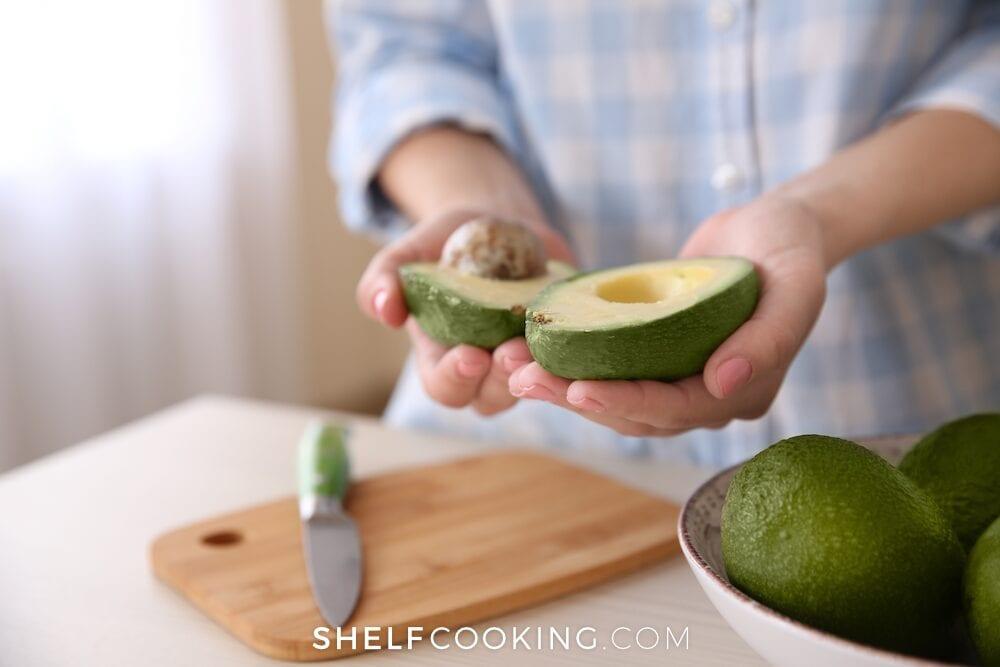 A halved avocado next to a bowl of avocados, from Shelf Cooking