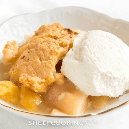 close up of a scoop of vanilla ice cream on top of peach cobbler, from Shelf Cooking