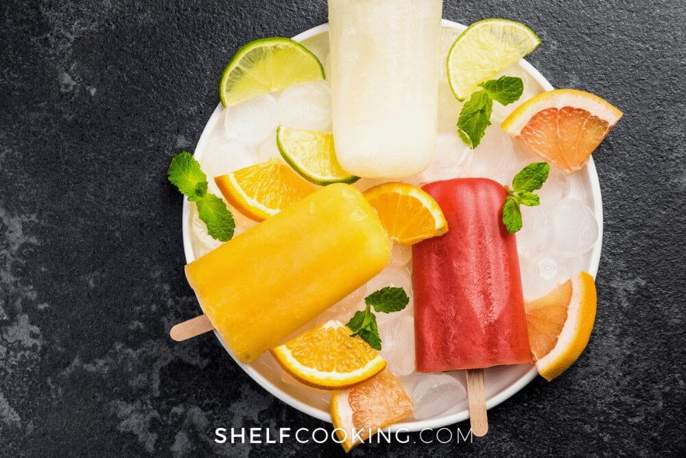 red and orange fresh fruit popsicles on a plate of ice, from Shelf Cooking
