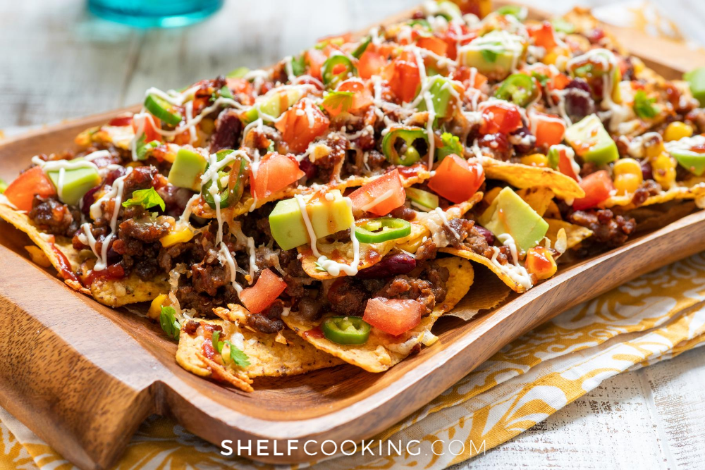 large plate of nachos with beans, cheese, avocados, and tomatoes