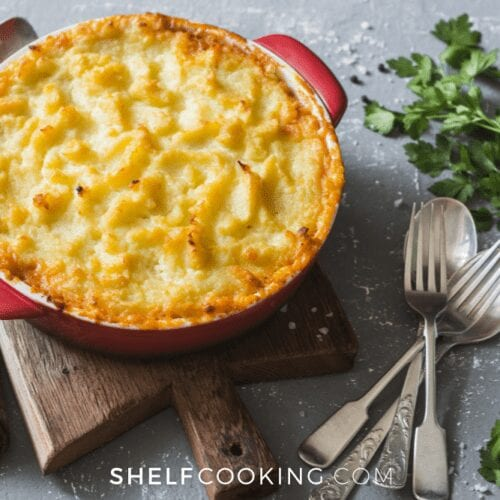 Baked Shepherd's Pie in a casserole dish on a cutting board, from Shelf Cooking