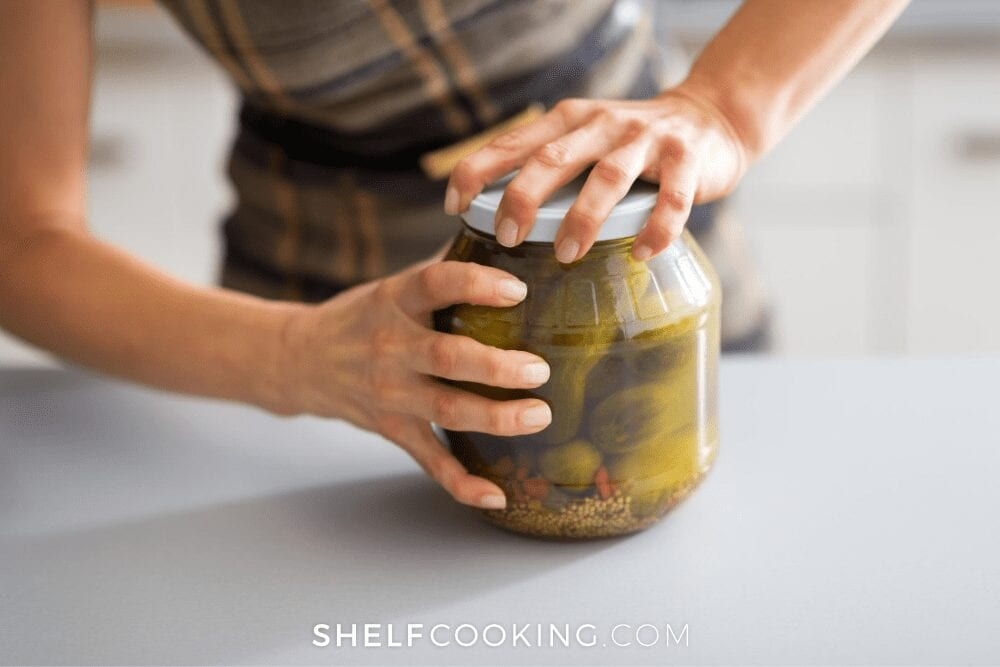 Woman taking the lid off a jar of pickles, from Shelf Cooking