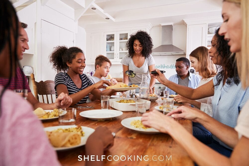 Two families sitting around a table eating dinner, from Shelf Cooking