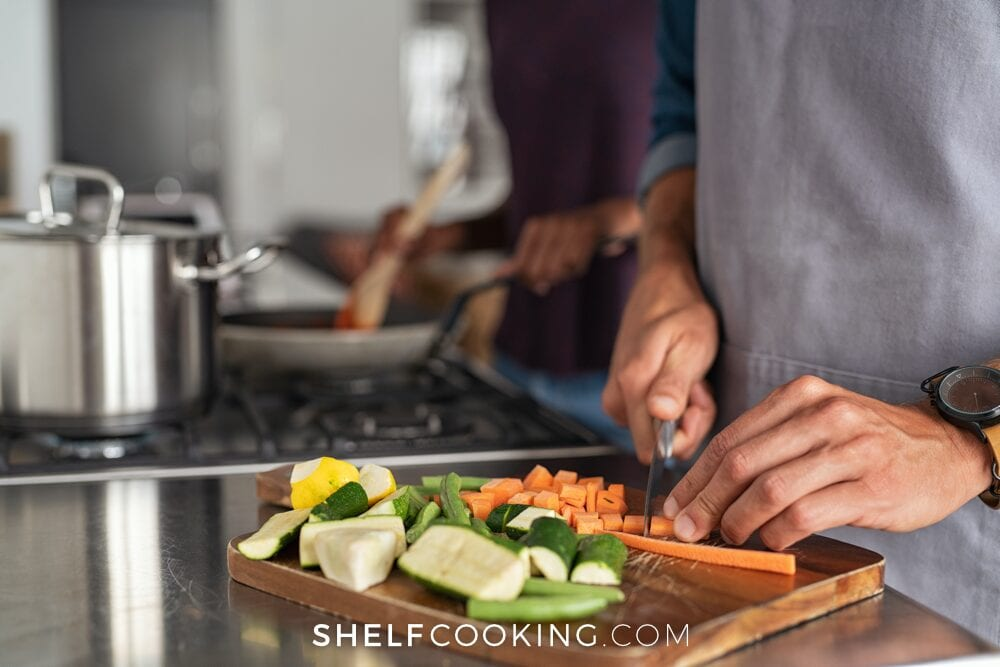 Woman cooking on the stove while man chops carrots, from Shelf Cooking