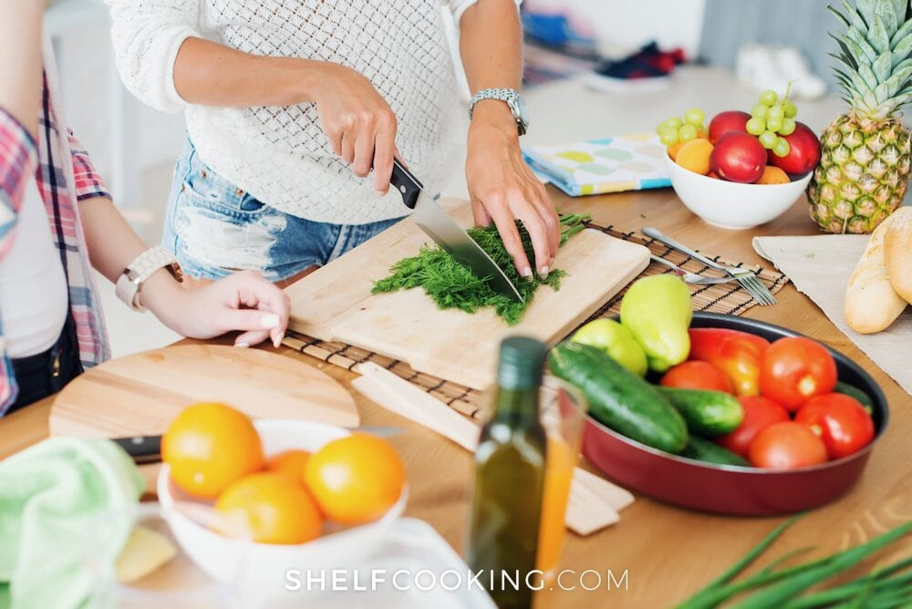 Woman's hands chopping herbs on a cutting board, from Shelf Cooking