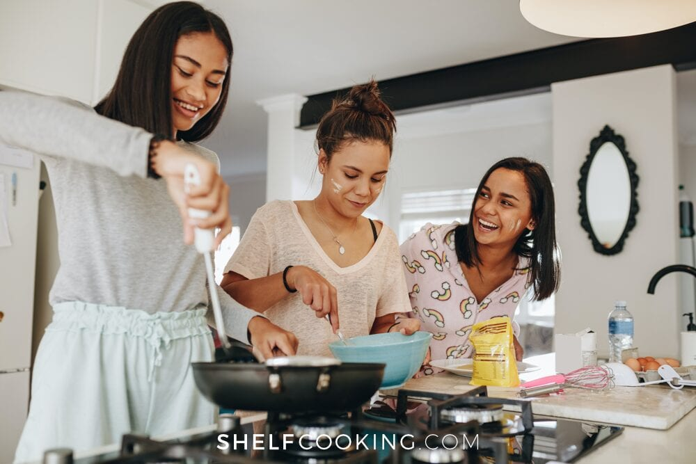 Three young ladies cooking food for teenagers, from Shelf Cooking