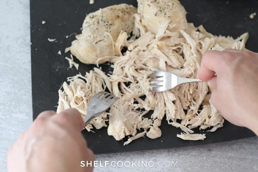 Hands shredding chicken with forks, from Shelf Cooking