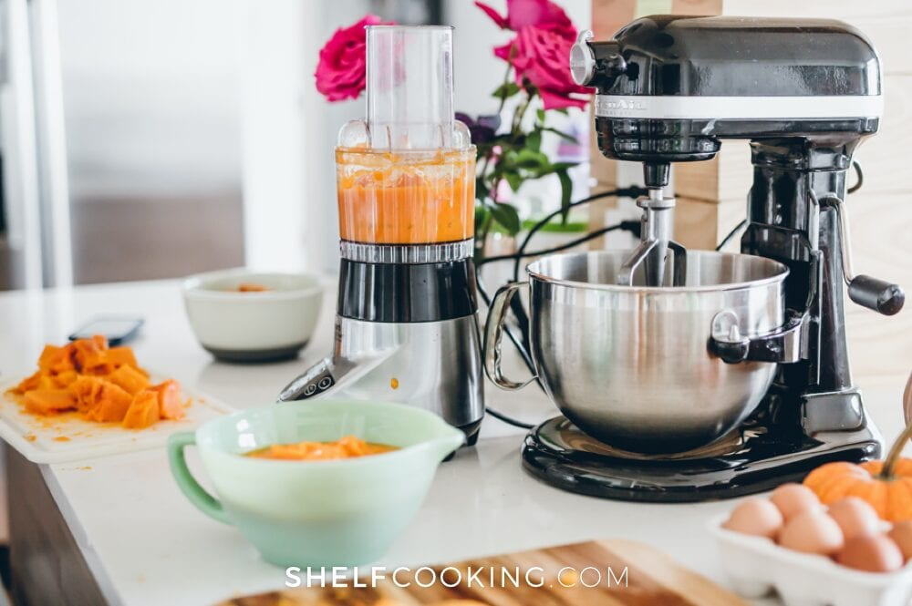 Food processor and bowl on a counter with pumpkin puree inside, from Shelf Cooking