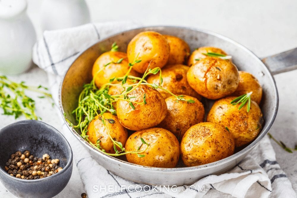whole potatoes in skillet on a dish towel and white countertop from Shelf Cooking