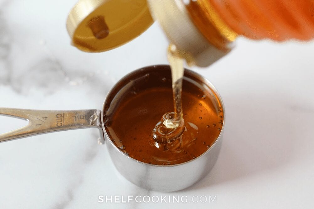 honey in a measuring cup on a white marble countertop, from Shelf Cooking