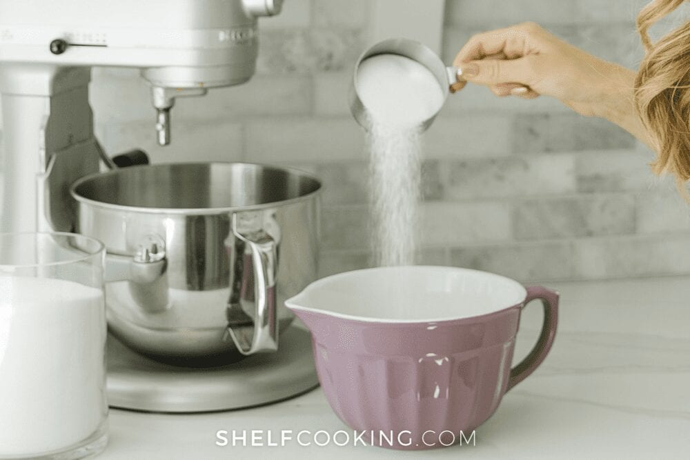 woman pouring white sugar into a mixing bowl, from Shelf Cooking