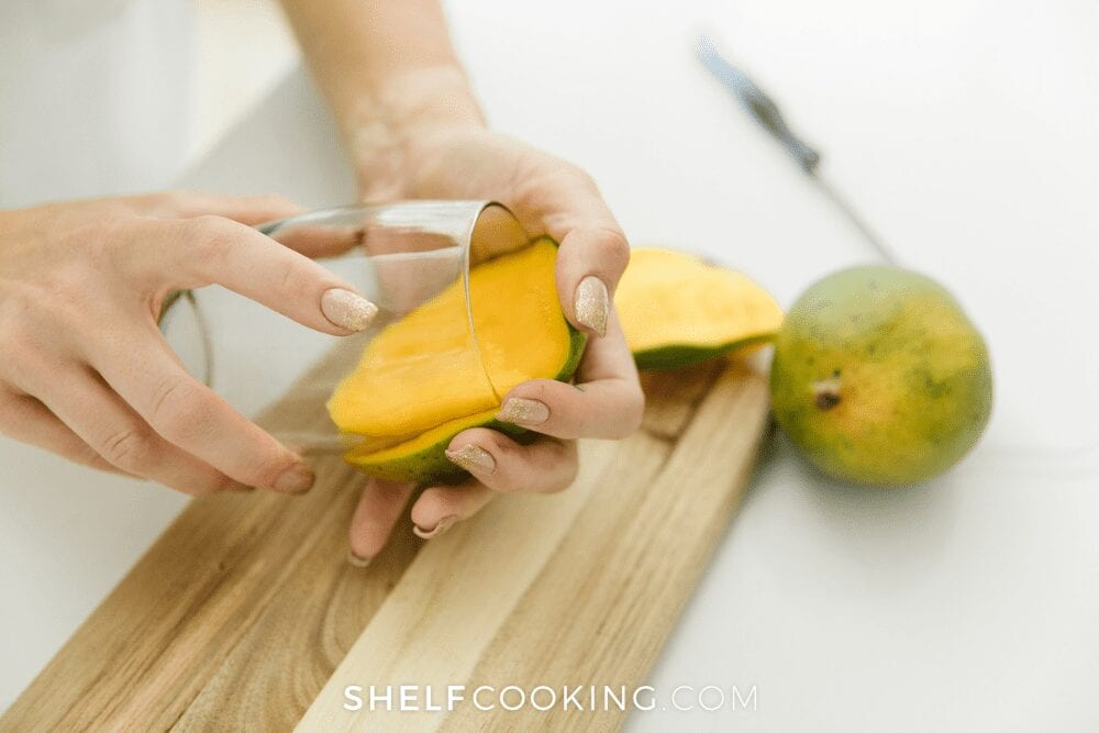 woman's hands peeling mango using a glass cup, from Shelf Cooking