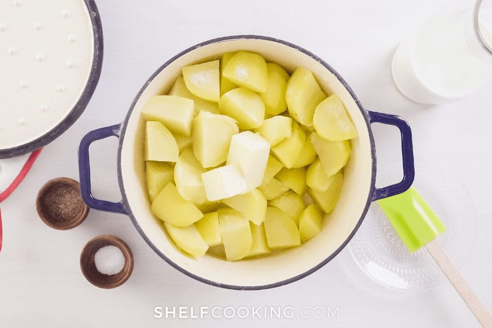 pot of cut boiled potatoes and butter for easy mashed potato recipe from Shelf Cooking