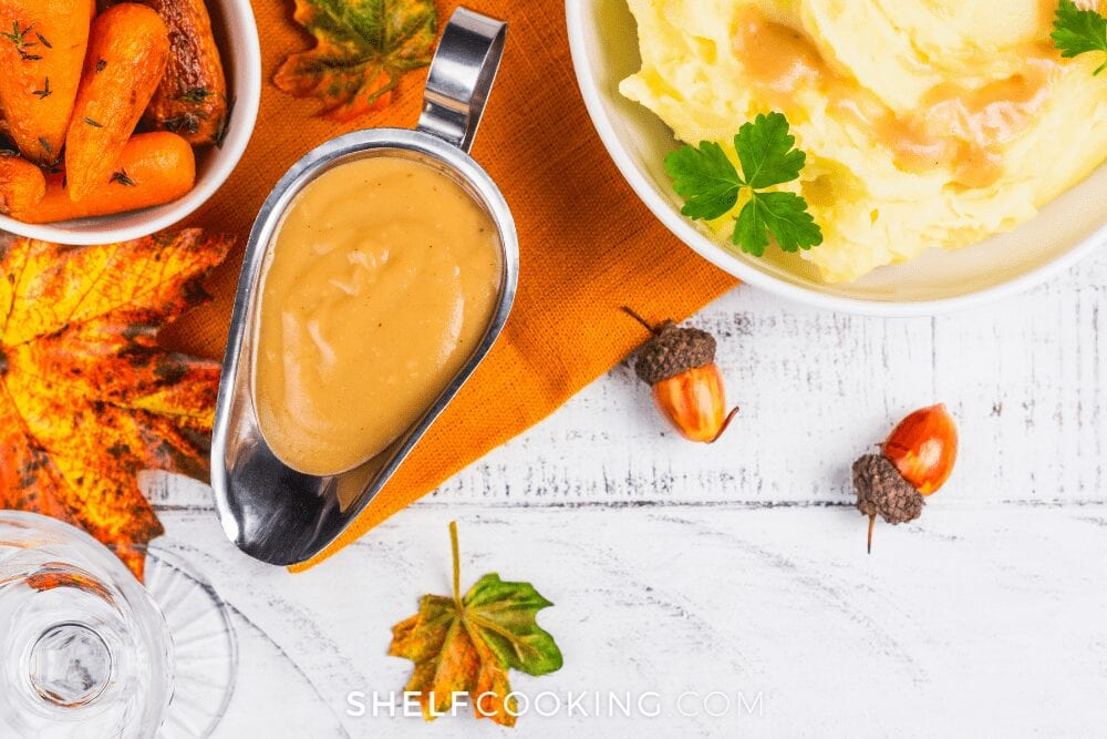 gravy boat with mashed potatoes on an orange tablecloth from Shelf Cooking
