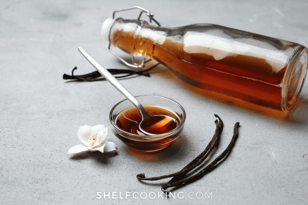 Vanilla extract in a jar with a small bowl with a spoon on a white counter from Shelf Cooking
