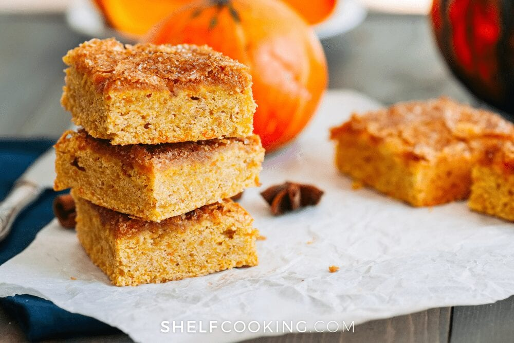pumpkin bars stacked together on top of a napkin from Shelf Cooking