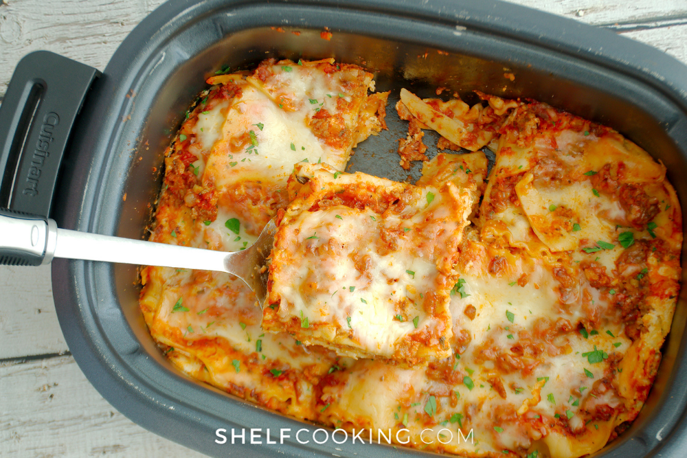 slicing crockpot lasagna with a spatula, from Shelf Cooking