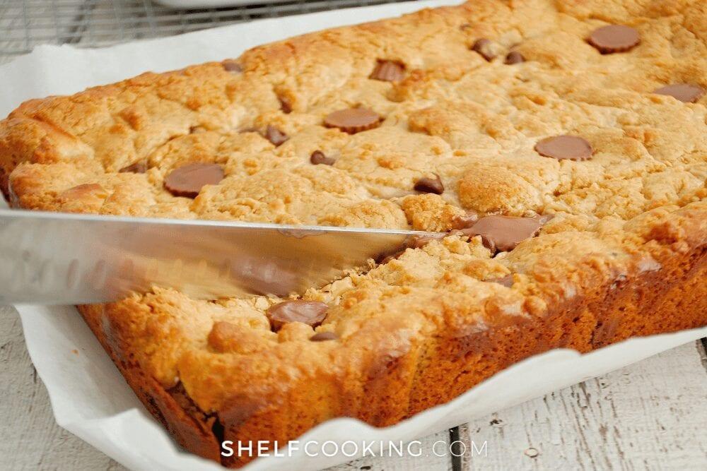 slicing homemade ooey gooey cookie bars, from Shelf Cooking