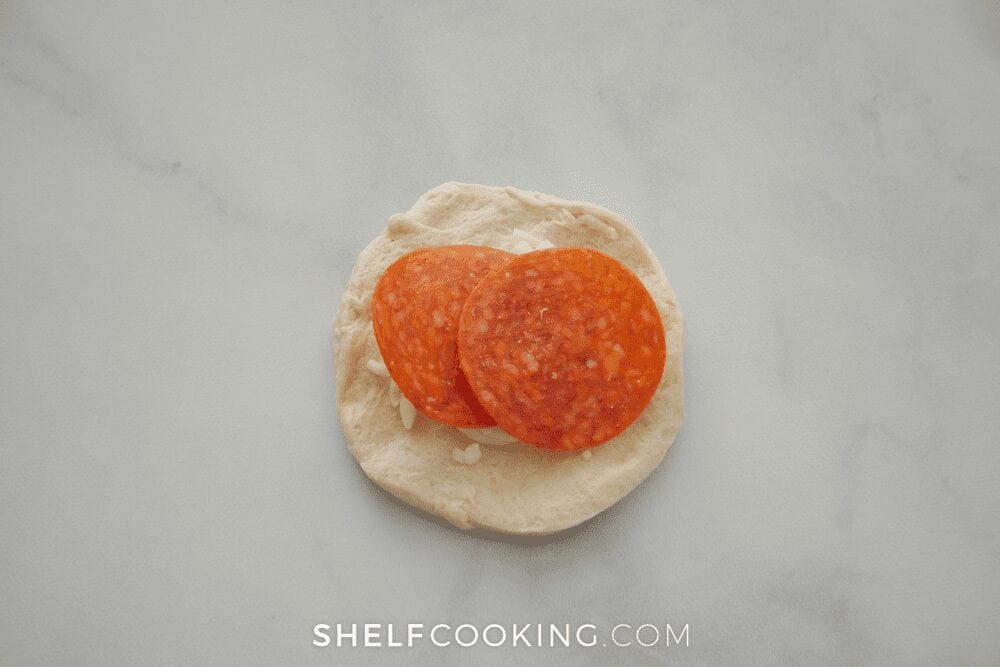 putting ingredients in pizza monkey bread, from Shelf Cooking