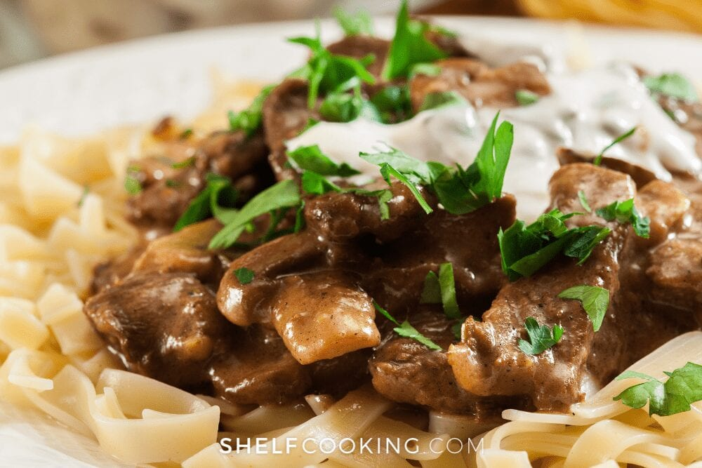 plate of homemade beef stroganoff with sour cream on top, from Shelf Cooking