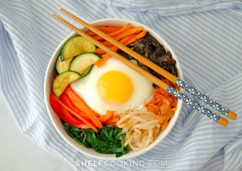 bibimbap recipe in a bowl with chopsticks, from Shelf Cooking