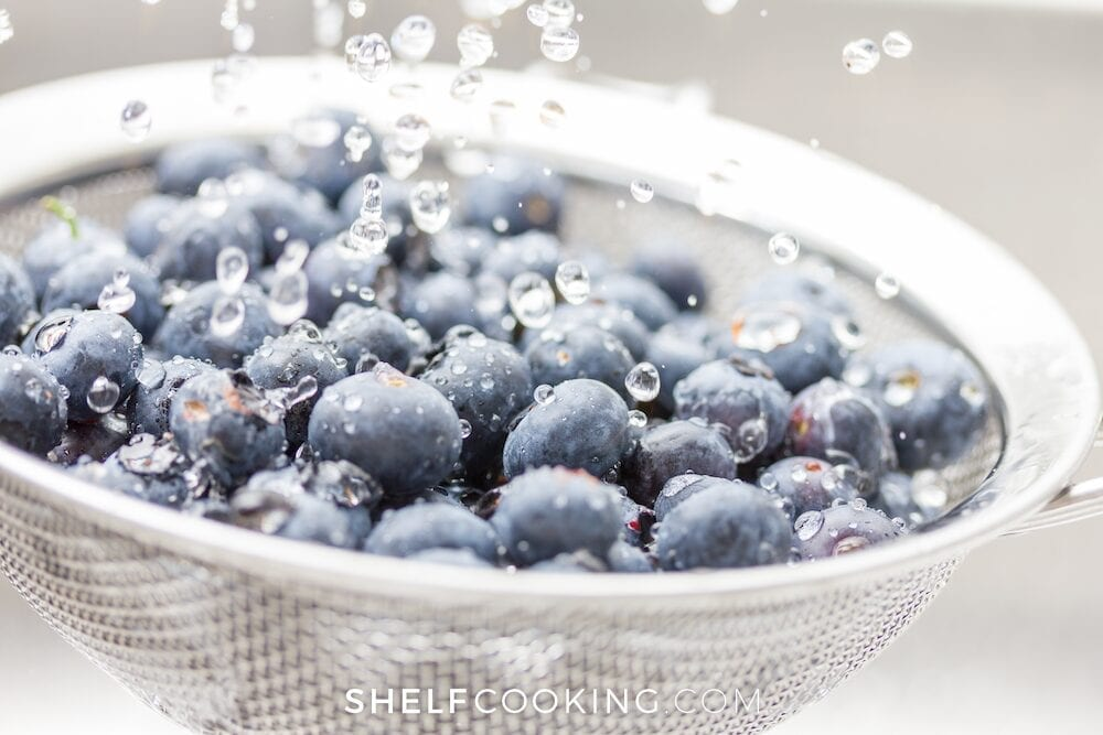rinsing blueberries in a colander, from Shelf Cooking