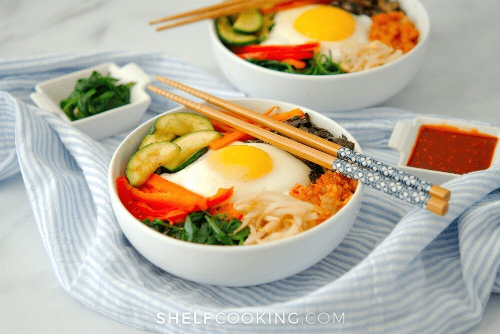 two bowls of bibimbap with chopsticks, from Shelf Cooking