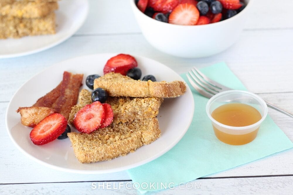 Crunchy French toast sticks on a plate with berries and bacon from Shelf Cooking.