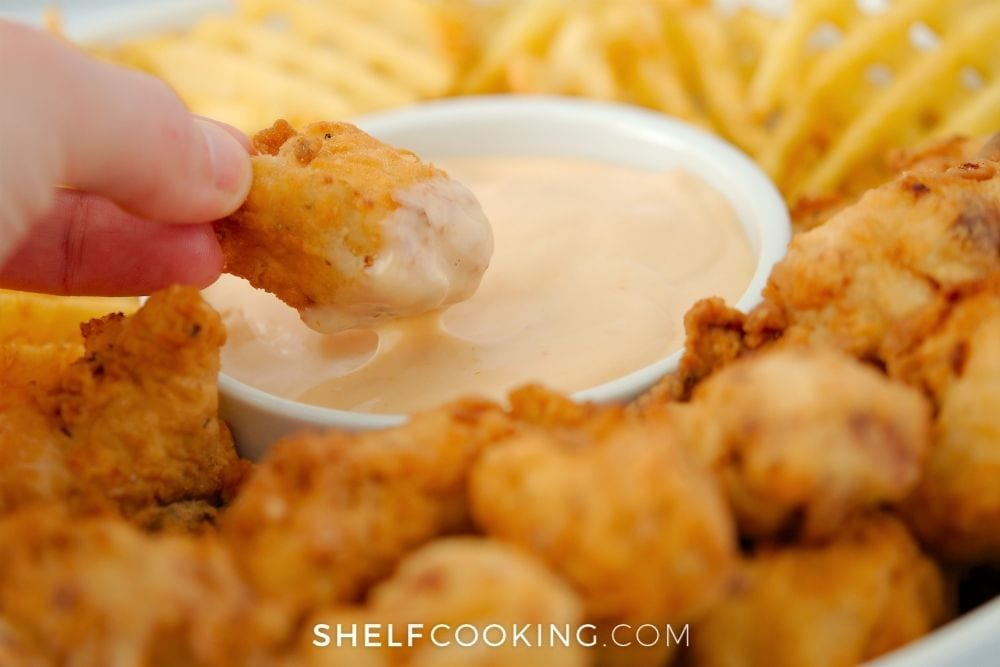 dipping a nugget in copycat Chick-fil-A sauce, from Shelf Cooking