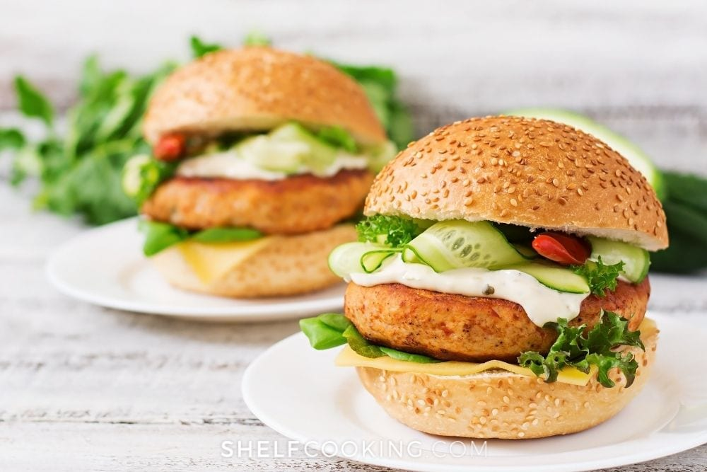 Ground chicken burgers on white plates with a variety of toppings from Shelf Cooking.