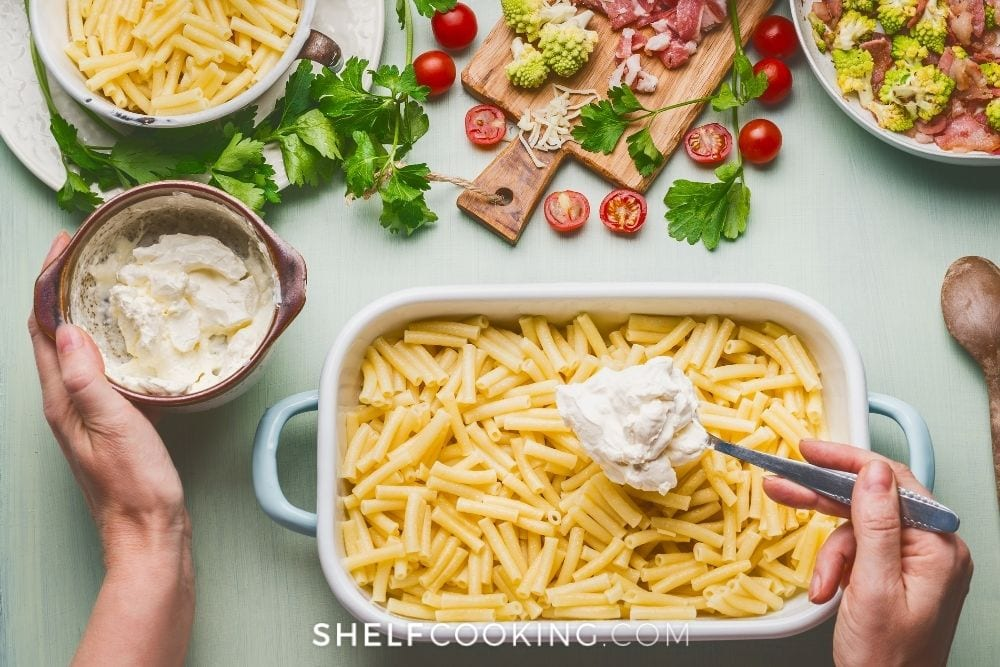 Hands assembling casserole for easy meal prep from Shelf Cooking.
