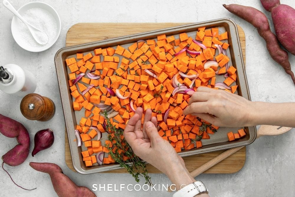 Hands placing chopped sweet potatoes and onions on a sheet pan for easy sheet pan recipes from Shelf Cooking.