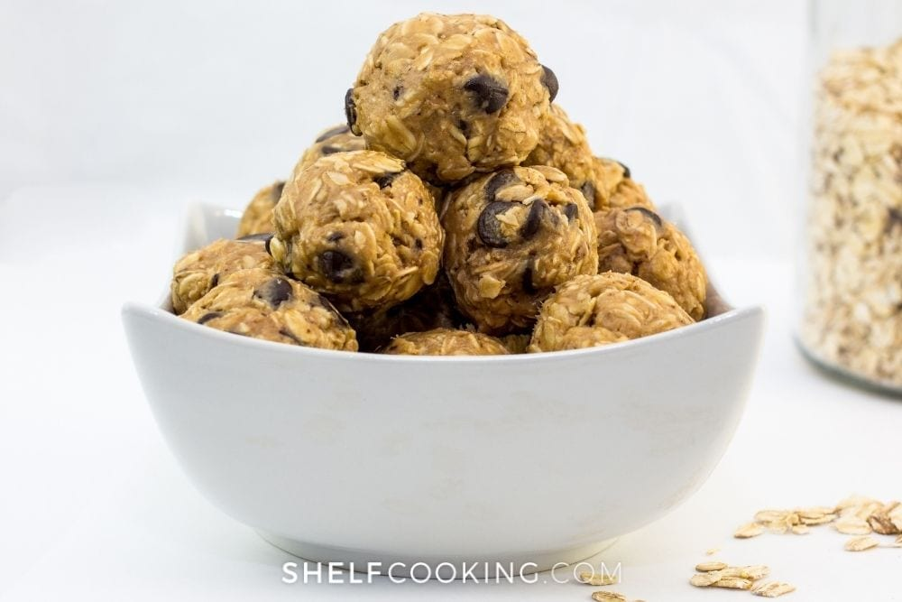 Energy bites in a white bowl from Shelf Cooking.