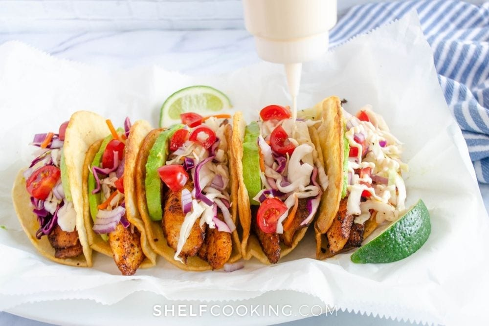 putting sauce on fish tacos, from Shelf Cooking