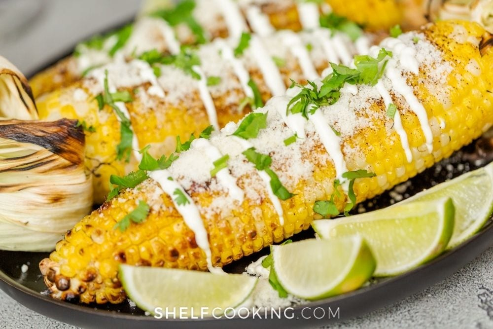 Grilled corn on the cob with sour cream and cilantro on top with sliced limes on the side from Shelf Cooking.