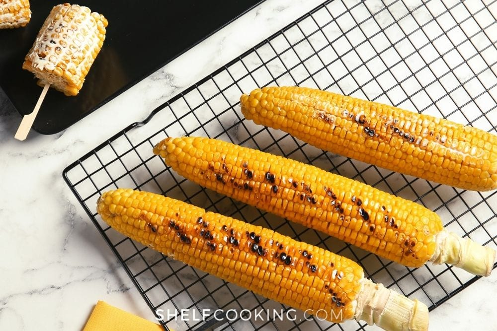 Grilled corn on the cob on a baking rack for how to cook corn on the cob from Shelf Cooking.